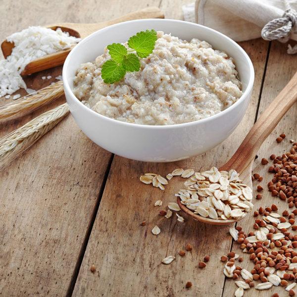 Bowl of various flakes porridge on wooden table